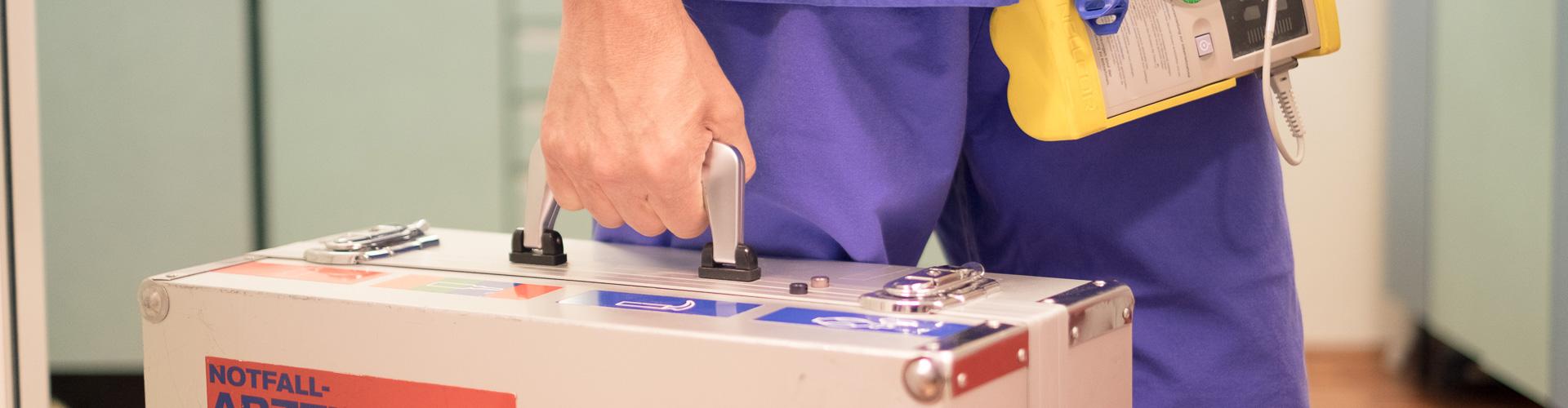 Hand hält Notfall-Arztkoffer