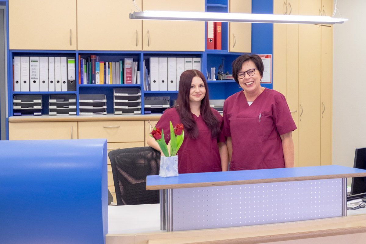 Zwei Mitarbeiterinnen stehen lächelnd am Empfang
